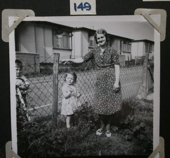Mrs Prosser with two small children in prefab garden | Hearn,Jane