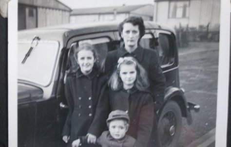 Woman with three children in front of car and prefabs
