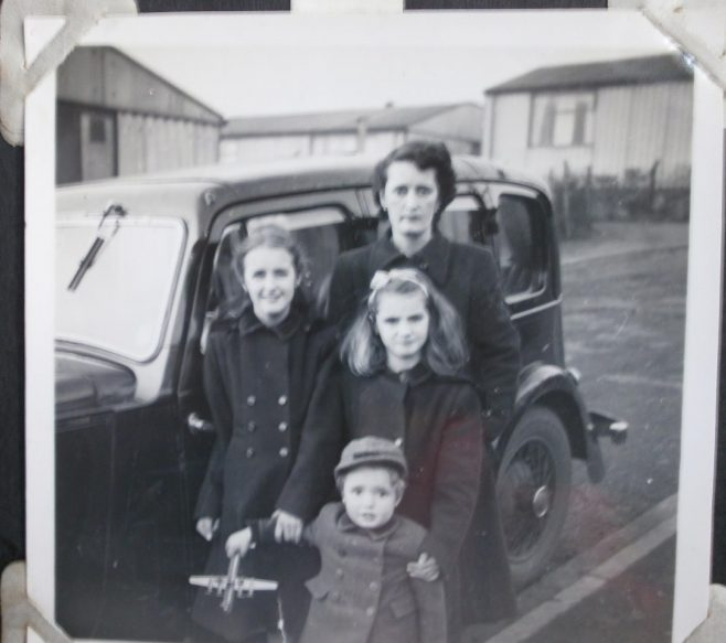 Woman with three children in front of car and prefabs | Hearn,Jane