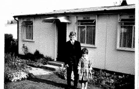 Photo of Allen and Judith Sawkins' family prefab (AIROH) in Farnham, Surrey, 50s, with brother and sister Allen and Judith in front of prefab
