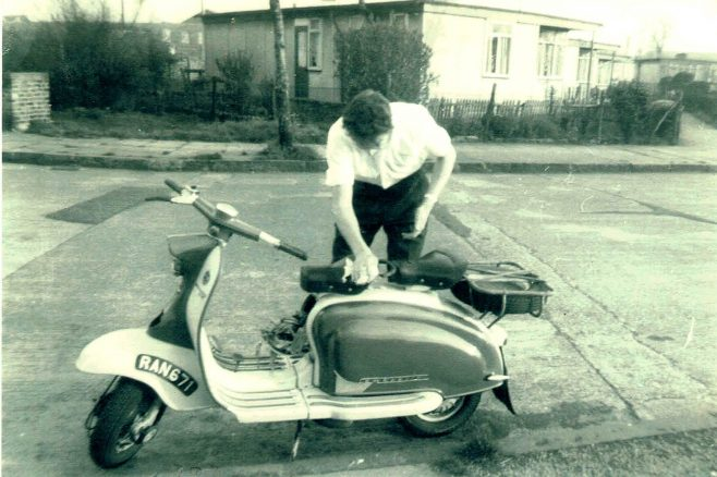 Bob Strudwick working on his scooter, taken from Mr and Mrs Marshalls prefab at No 6, Strattondale Street, Isle of Dogs, London 50s or 60s | Hearn,Jane