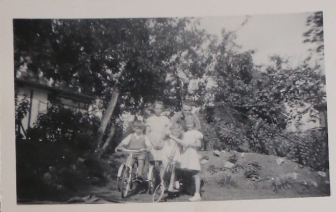 Four children, an adult and two bikes on the prefab estate at Willesden | Hearn, Jane