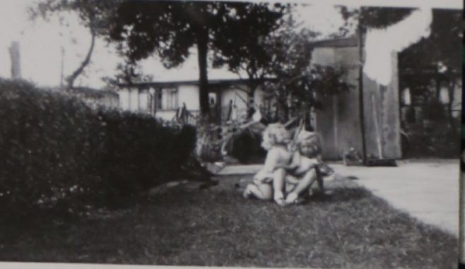 Two small children in the prefab garden in Willesden | Hearn, Jane