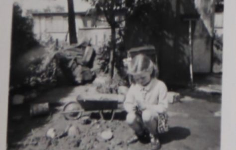 Penny Bishop as a small child playing with a toy wheelbarrow in the prefab garden