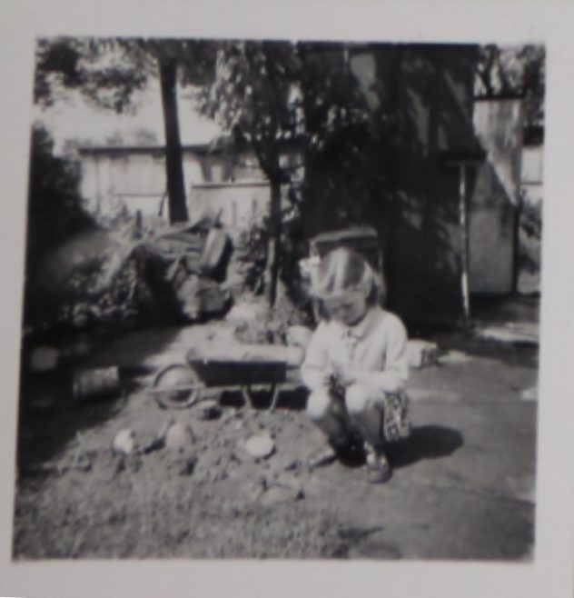 Penny Bishop as a small child playing with a toy wheelbarrow in the prefab garden | Hearn, Jane