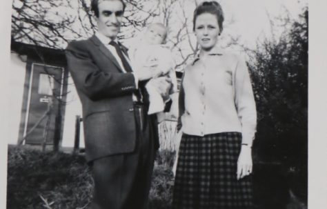 Penny Bishop as a baby with her mum and dad outside their prefab