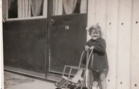 Kathryn with pushchair and doll in front of prefab