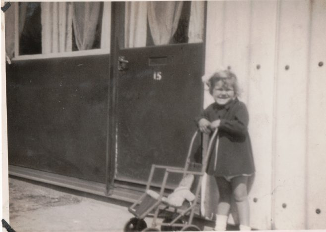 Smail girl with pushchair and doll in front of prefab | Hearn, Jane