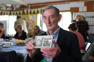 Ray Smith holding photos of his family prefab in Penarth, South Wales at the Excalibur at 70 event, 2016 | Prefab Museum
