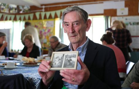 Ray Smith holding photos of his family prefab in Penarth, South Wales at the Excalibur at 70 event, 2016