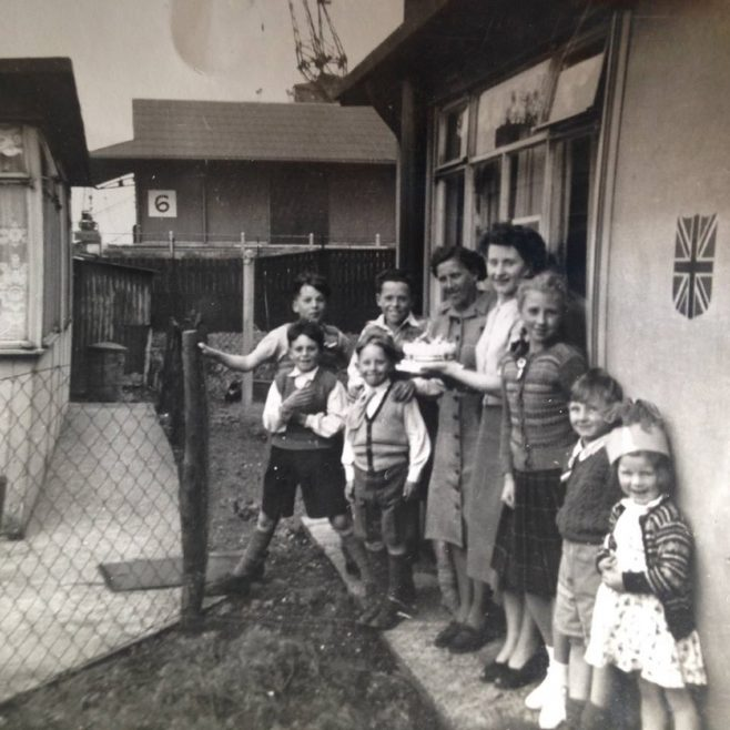 Family group outside a prefab decorated for the coronation, Albert Road, North Woolwich | Hearn, Jane