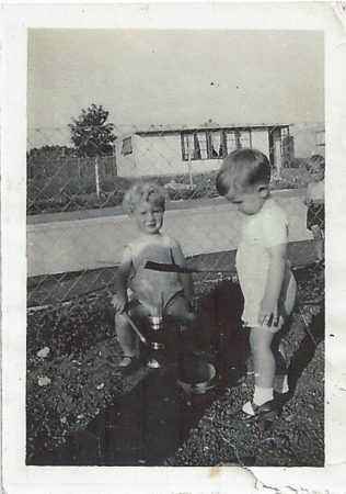 Two small children playing with buckets and spades in the prefab garden, Clement Road | Christine and Peter Bedell