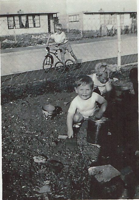 Two small children playing in the prefab garden, one in background on bike | Hearn, Jane