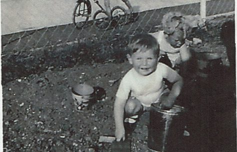 Two small children playing in the prefab garden, one in background on bike. Clement Road, Willesden