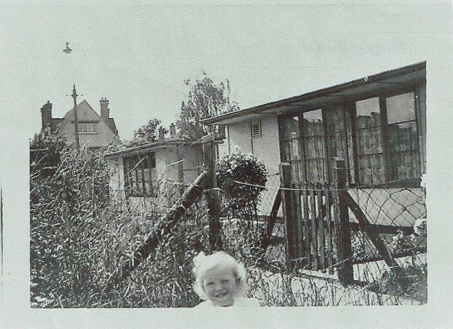 Small child in prefab garden in Willesden | Hearn, Jane