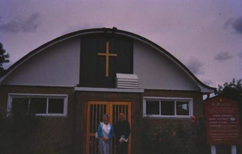"Photograph of a man and a woman, probably Alan's mum, from the Brine family in front of St Mark's Church, the ""Prefab Church"""