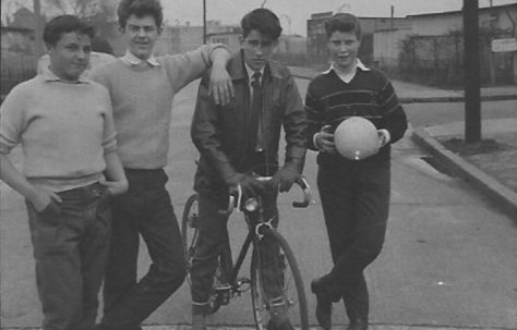 Four teenage boys, one on a bike, in front of prefabss. Stewart Street, London E14