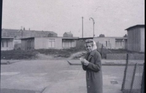 Woman standing in street in front of prefabs. Stewart Street, London E14