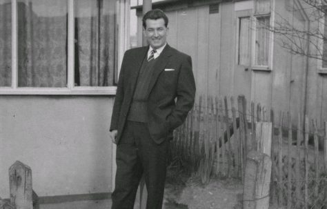 Man In suit standing in front of prefab.  Stewart Street, London E14