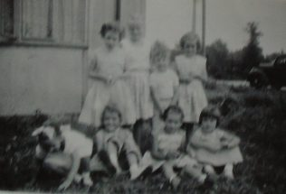 Group of eight children in front of Uni-Seco prefab, Silver End