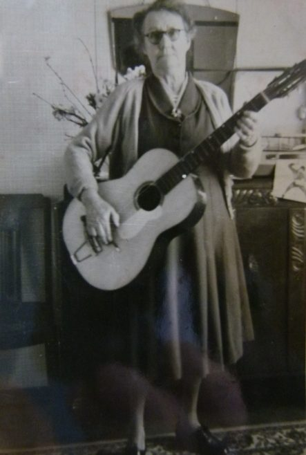 Grandma playing guitar in prefab, 401 Wake Green Road, Moseley