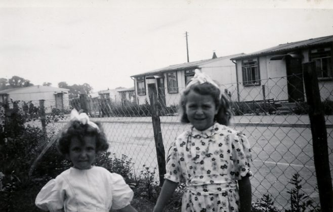 Two little girls in a prefab front garden on the Harold Hill estate