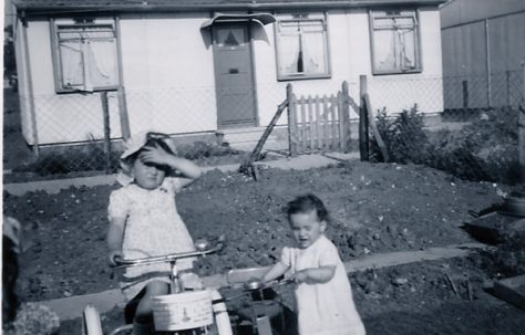 Two little girls, one on a bike, in front of a prefab on the Harold Hill estate