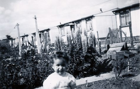 Little girl in front of prefabs on the Harold Hill estate