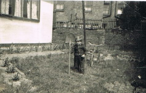 Alf with a big shovel and bike in the prefab garden at Narford Road, London E5