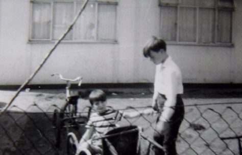 Two boys, one in a bicycle trailer, outside the prefab at Underhill Road, London SE22
