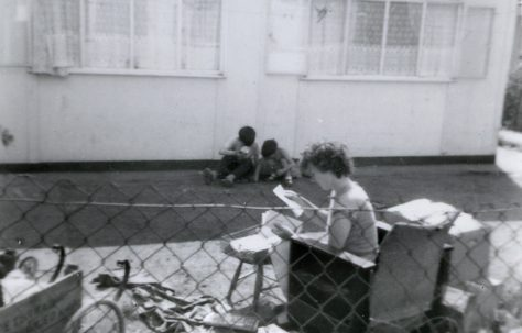 Woman and two boys in the garden of a prefab in Underhill Road, London SE22