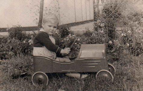 Boy racer. Ben in a toy car outside his prefab in Dartmouth Park Hill, London N19