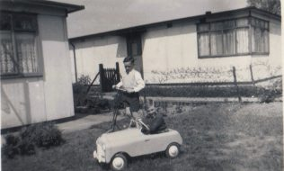 Terence and small boy in toy car in the prefab garden, Dartmouth Park Hill, London N19