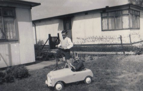 Terence on his scooter and neighbour Raymond in toy car in the prefab garden, Dartmouth Park Hill, London NW5