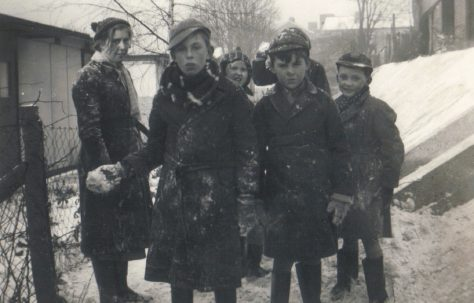 A group outside the prefabs in the snow, Dartmouth Park Hill, London N19