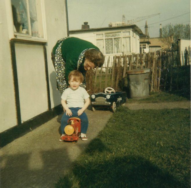 Paul sitting on a toy train, with his grandmother, in the prefab garden. Berthon Street, Deptford, London SE8