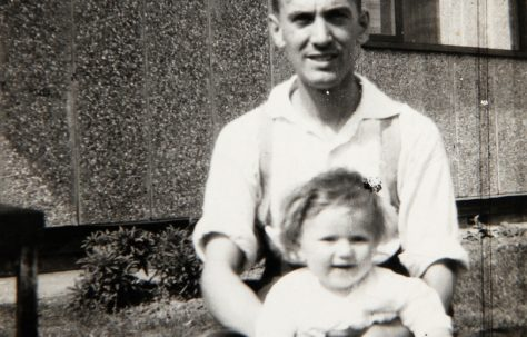 Dad with baby outside Tarran prefab. Bolsover, Derbyshire