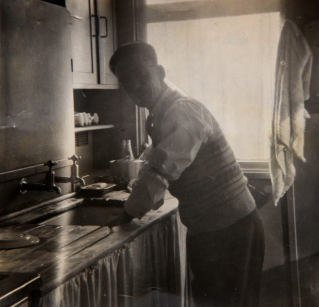 Dad washing up in prefab kitchen. Bolsover, Derbyshire