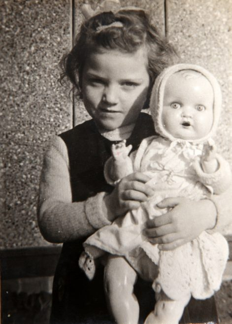 Pat holding her doll in the prefab kitchen. Bolsover, Derbyshire