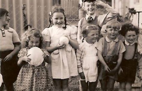 Seven smiling children by the coal shed. Hollyhedge bungalows, Blackheath, London SE3