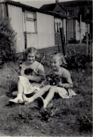 Two girls with kittens in the prefab garden. Hollyhedge bungalows, Blackheath, London SE3 | Brenda Anderson Browne