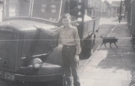 Older brother Harry in Tooke St standing outside our prefab which is out of view to the right. Another prefab(one of four here) is visible through the windscreen of the lorry.