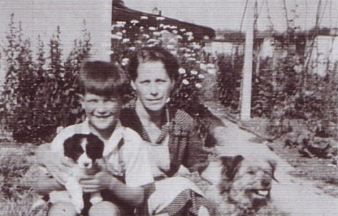 Jim and his mum with two dogs, runner bean canes in the background. Excalibur Estate, London SE6