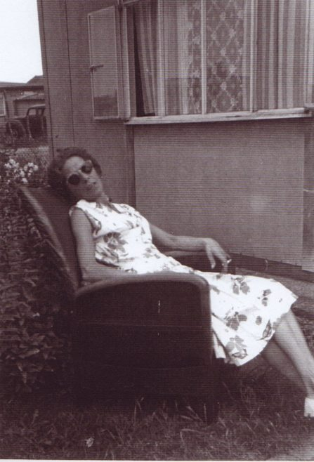 Jim's mum sitting in a chair in the prefab garden. Excalibur Estate, London SE6