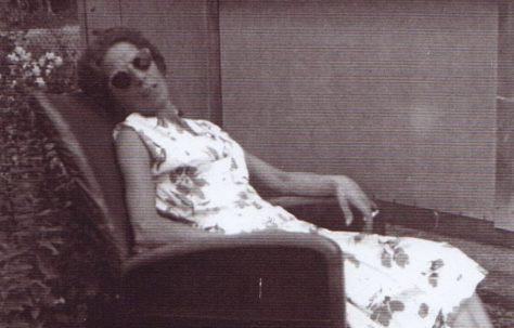 Jim's mum sitting in a chair in the prefab garden. Excalibur Estate, London SE6