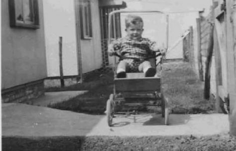 Bob in his pushchair outside the prefabs. Barnfield Road, St Mary Cray