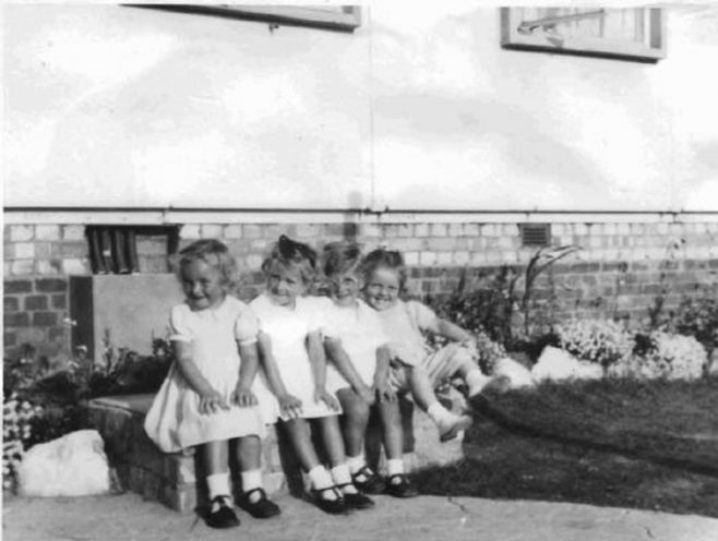 Four toddlers sitting on a wall. Barnfield Road, St Mary Cray