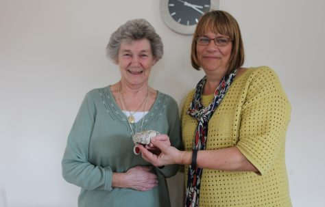 Portrait of Peggy holding a piece of her old prefab, with Siobhan from Rykneld Homes