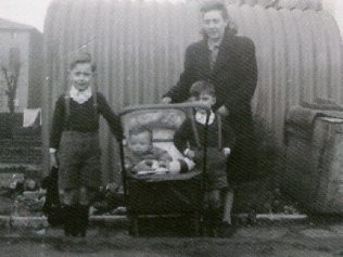 Mum and we three boys, posing outside the Anderson shelter. This would have been in 1948, judging by my physical size in the pram. To the left is the back of a house in Richmond Avenue. | Ray Watts