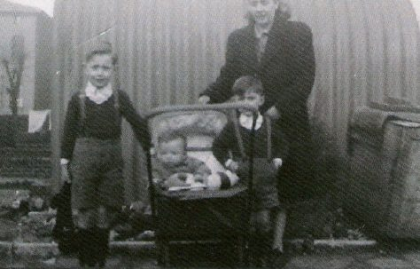 Mum and we three boys, posing outside the Anderson shelter. This would have been in 1948, judging by my physical size in the pram.